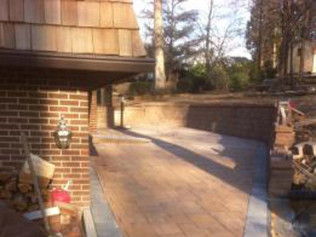 Brick paver patio with retaining wall and concrete curb